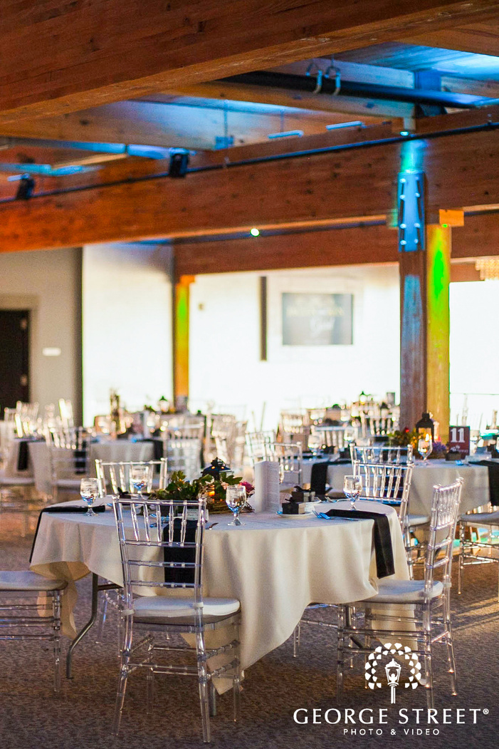 white talbe with black napkins and transparent chairs in bright reception room with wooden ceiling