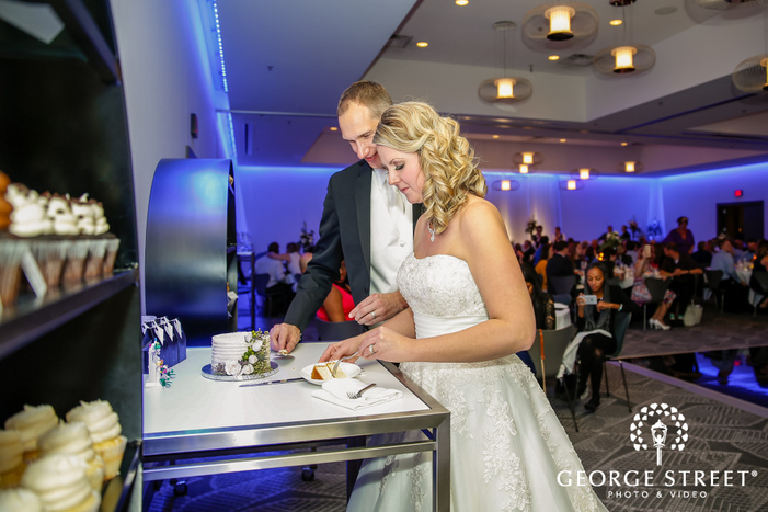 cheerful couple cutting cake in reception wedding photos