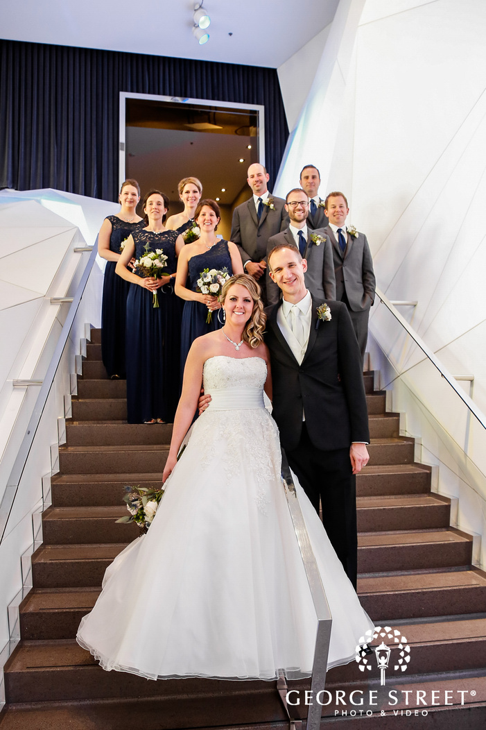 joyful bride and groom with friends on stairs at radisson blu mall of america wedding photography