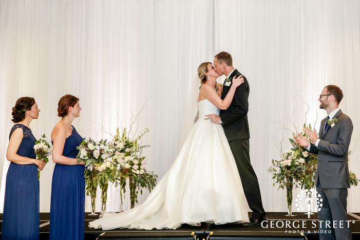 loving bride and groom first kiss at wedding ceremony altar radisson blu mall of america