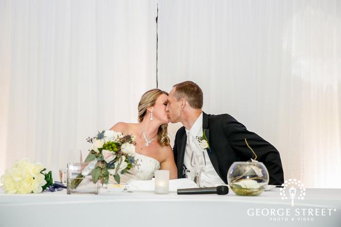 romantic couple kiss at reception table wedding photo