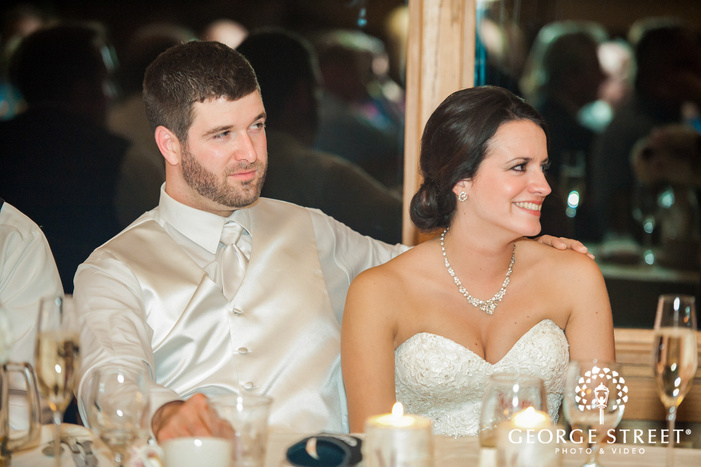 cheerful bride and groom during reception toast wedding photo