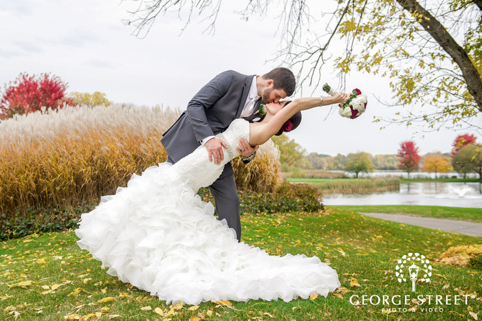 passionate bride and groom near green meadows and trees at mendakota country club in minneapolis