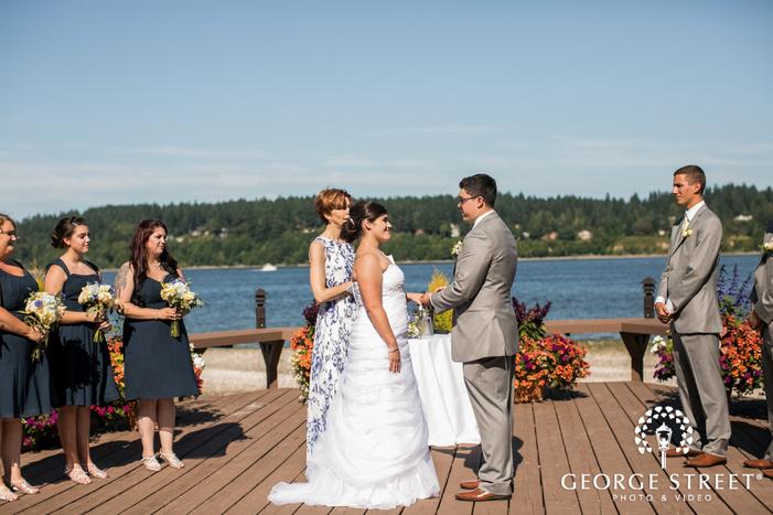 charming bride and groom wedding rings exchange at lake side in seatlte wedding photo