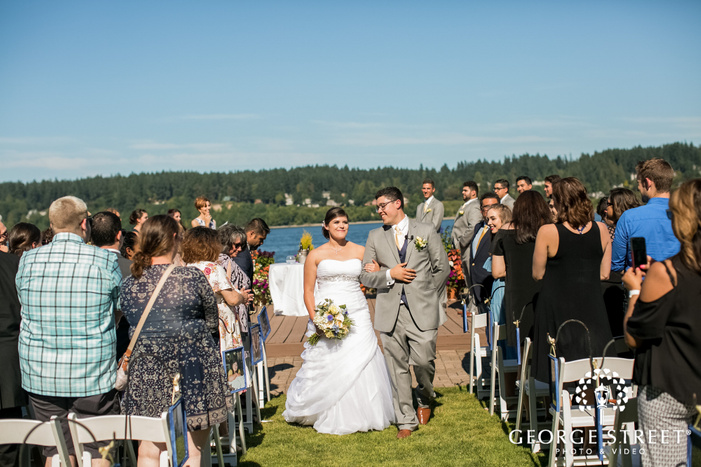 joyous bride and grom marching out the aisle in seatlte wedding photo