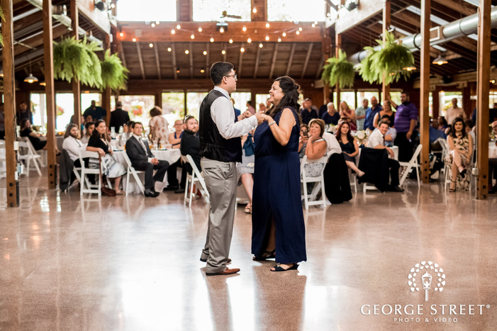 lovely groom and mother dance in reception hall wedding photo
