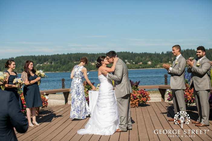 passionate bride and groom first kiss at wedding ceremony outside kiana lodge in seatlte wedding photo