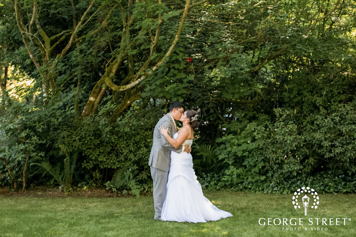 romantic bride and groom kiss in wedding venue lawn wedding photography