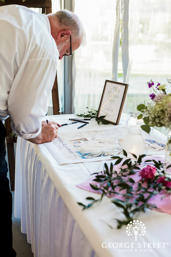 happy guest signing for couple at reception