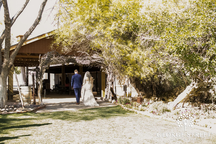 cute newly wed couple walking out ceremony venue in phoenix wedding photo