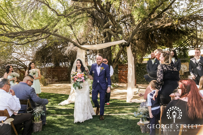excited bride and groom marching out the aisle at whispering tree ranch in phoenix wedding photo