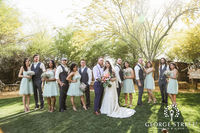 jovial couple and group at front yard of whispering tree ranch wedding photography