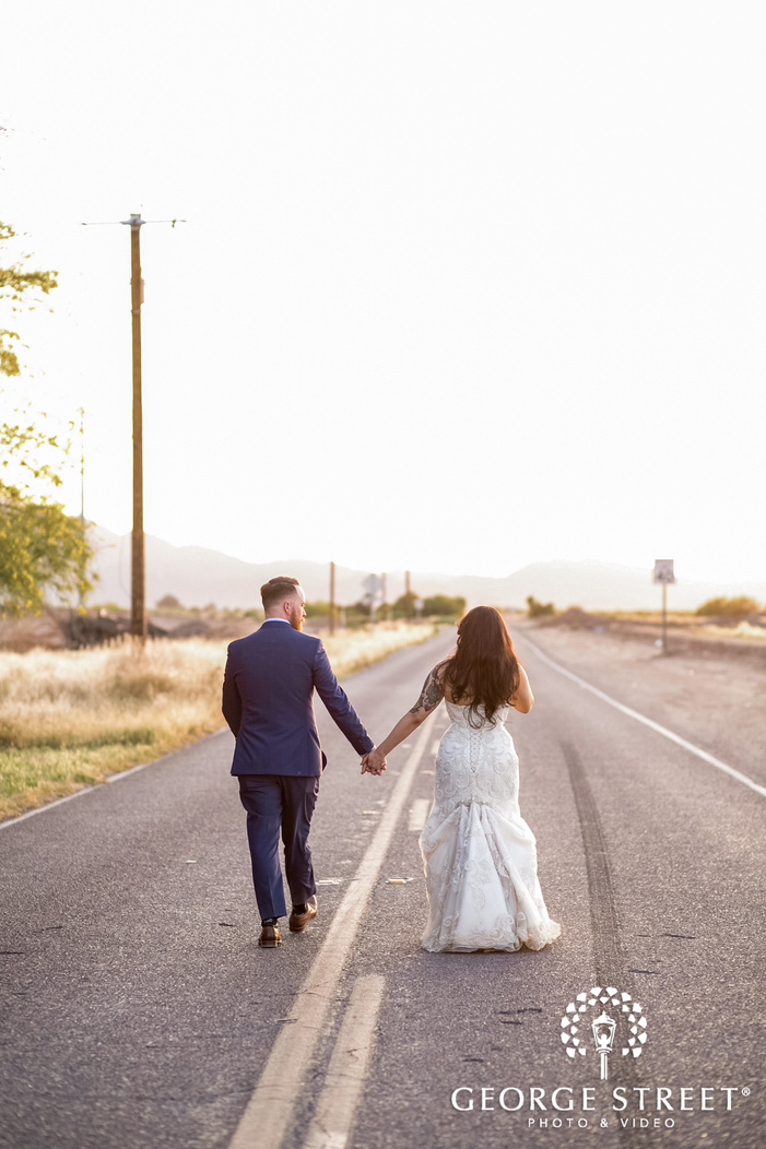 lovely bride and groom walking on road at whispering tree ranch in phoenix wedding photography