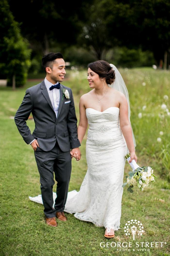 joyful bride anbd groom walking in lawn             s