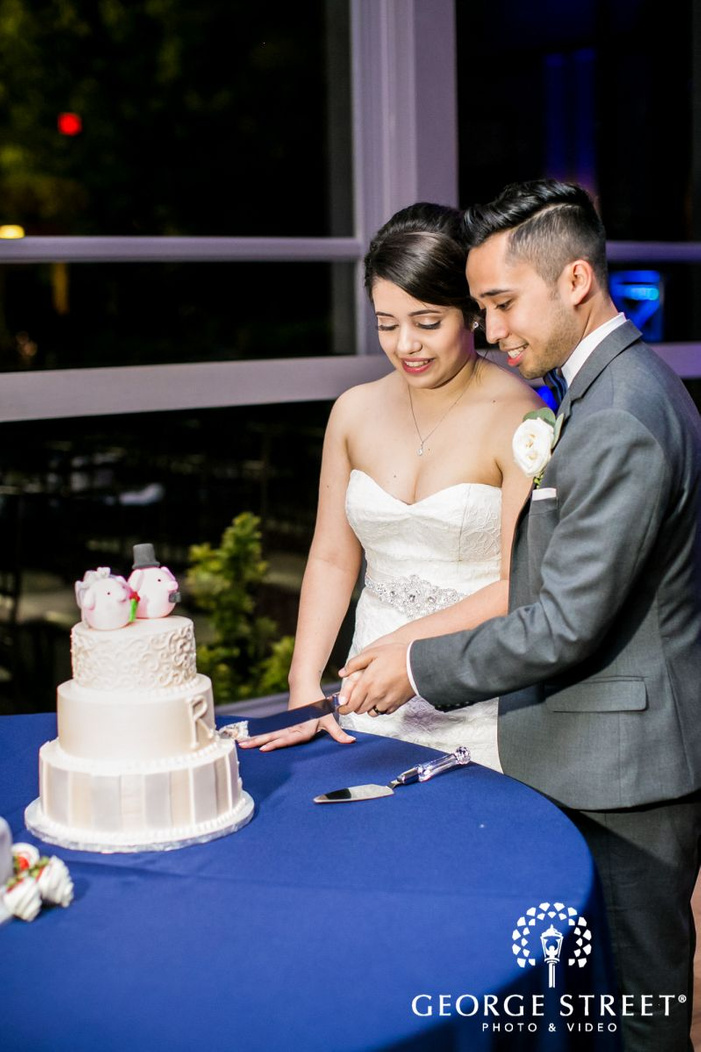 stunning bride and groom at cake cutting ceremony             s