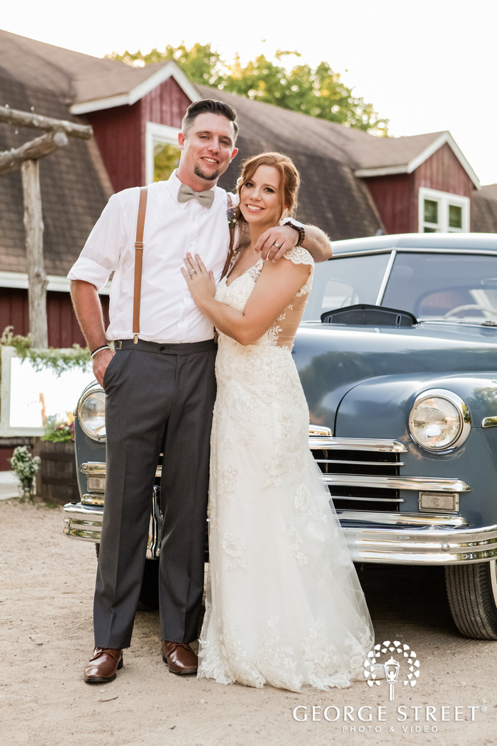 attractive bride and groom infront of car