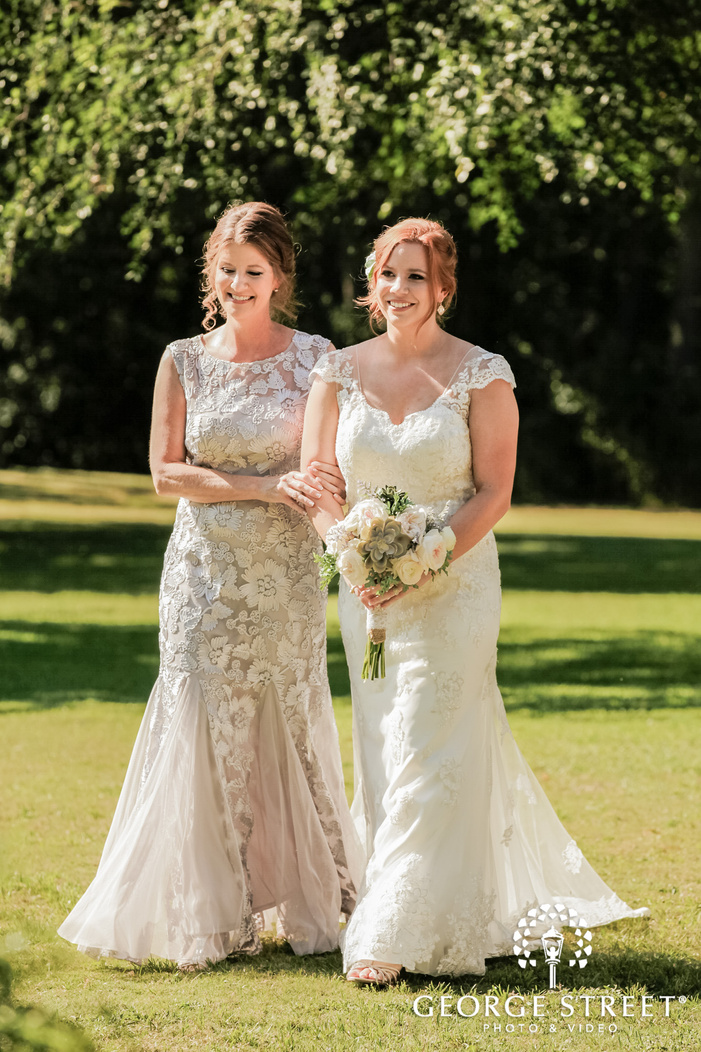 attractive bride and mother walking down the aisle