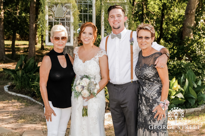 joyful bride and groom with mother and guest