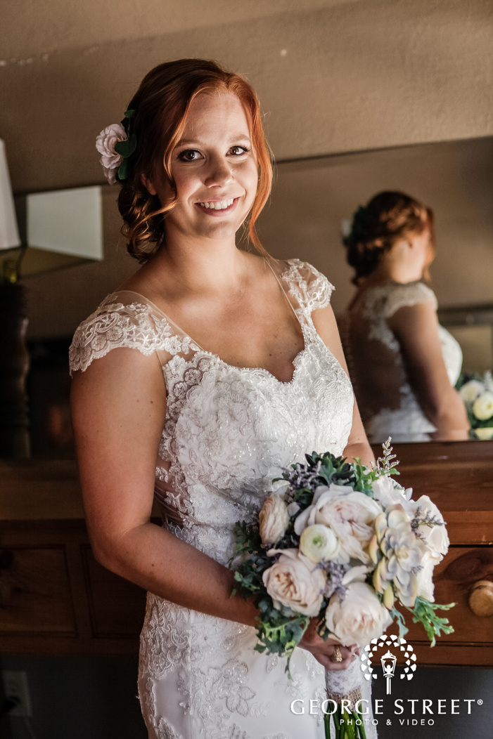 pretty bride with lovely bouquet in room