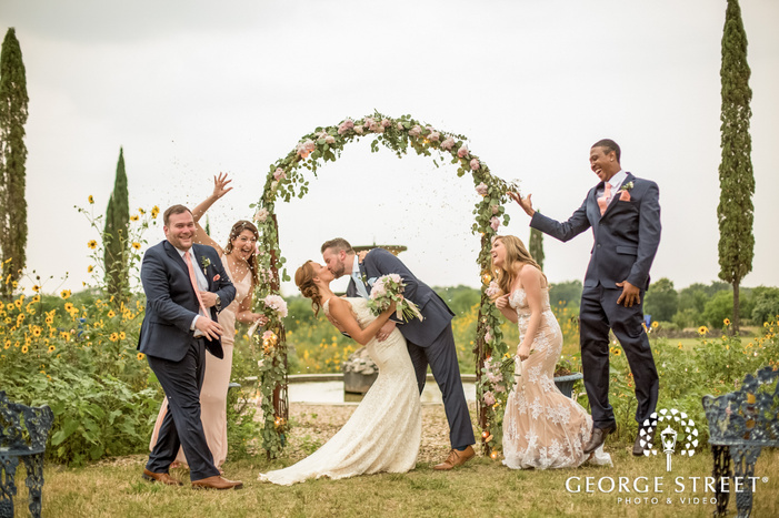 loving couple with bridesmaids and groomsmen in yard