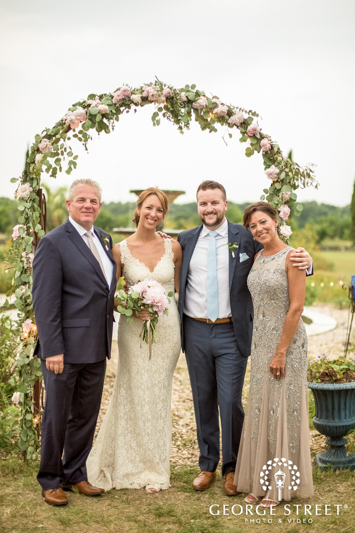 pretty bride and groom with parents