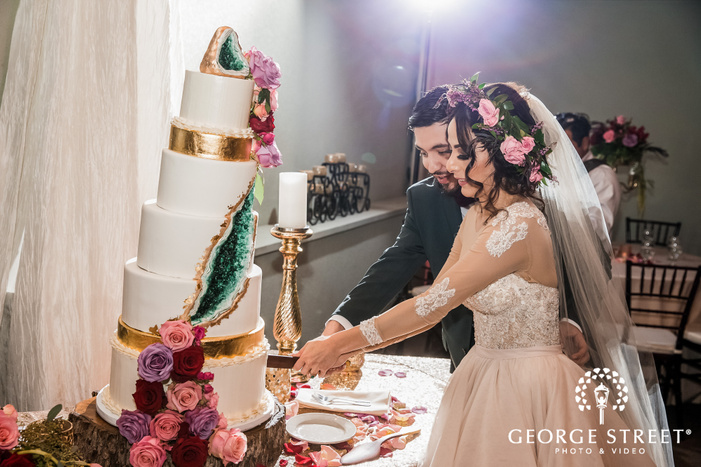 good looking bride and groom at cake cutting ceremony