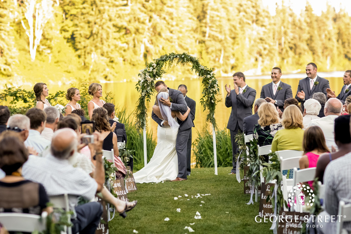 romantic bride and groom first kiss at lake wilderness lodge in seattle
