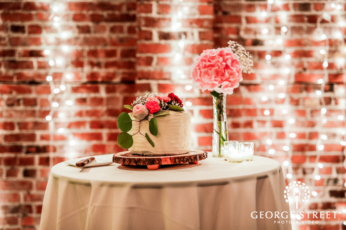 delightful one tier cake with floral topper wedding photo