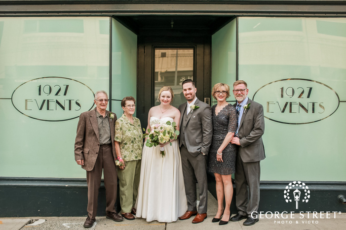 happy couple and guests in front of hotel wedding photo