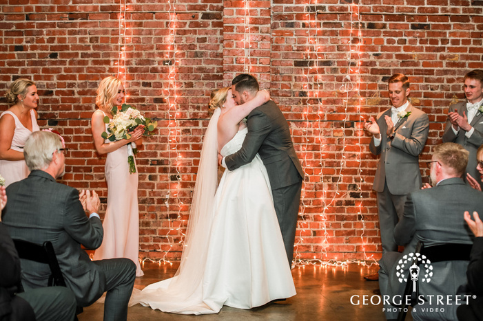 passionate bride and groom first kiss wedding photo