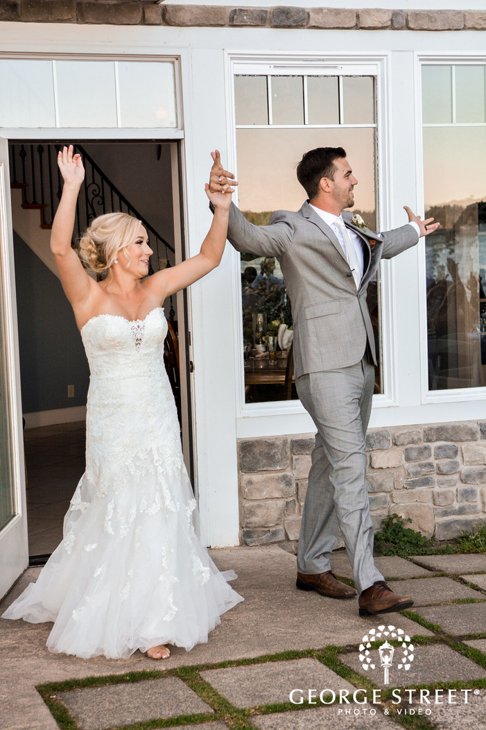 cheerful bride and groom at reception entrance