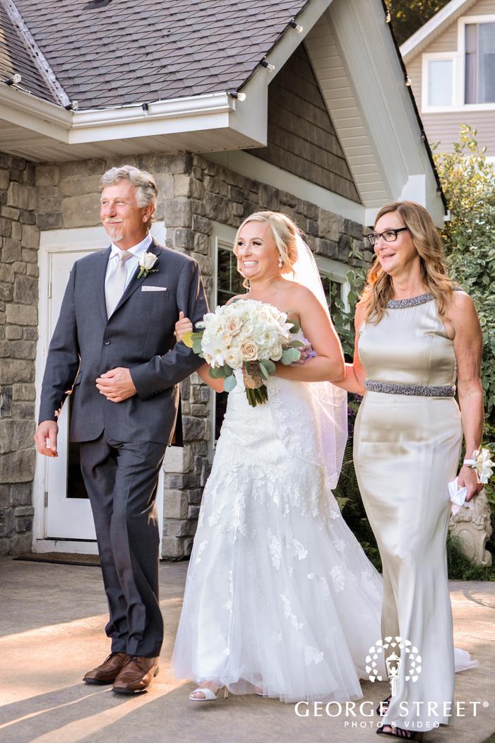 gorgeous bride and parents walking down the aisle