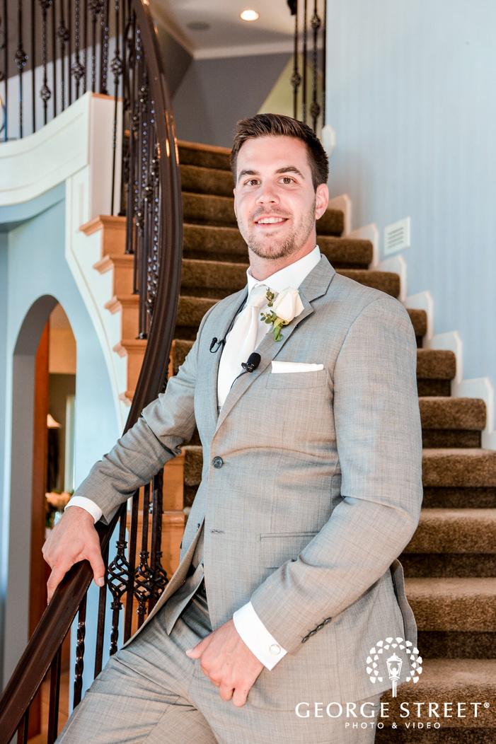 happy groom posing on stairs