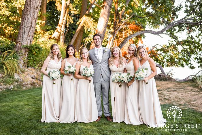 joyful groom and bridesmaids in yard