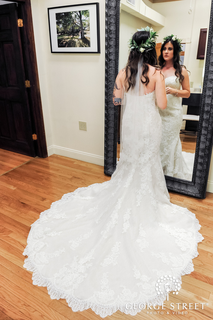 brides final touch ups in front of a mirror wedding photo