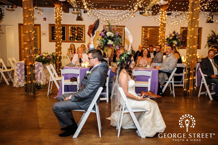 cheerful bride and groom playing reception games wedding photo