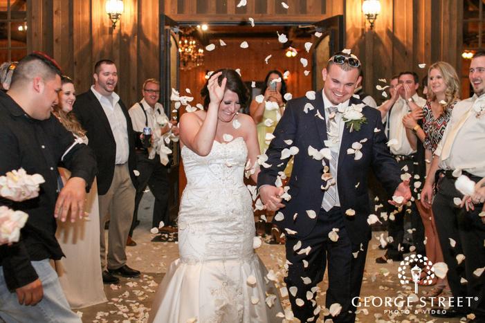 bride and groom reception sendoff with rose petals