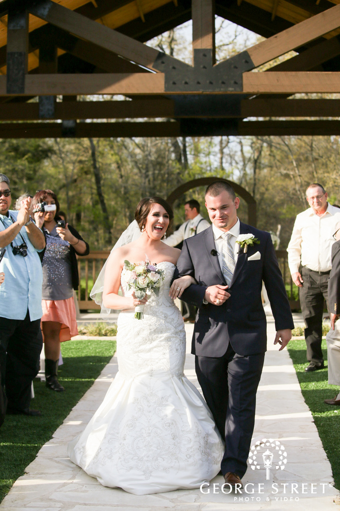 laughing bride and groom leaving wedding ceremony