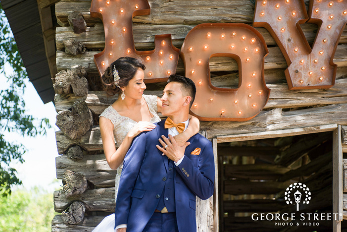 pecan springs ranch austin beautiful sunny outdoor bride and groom portraits love sign