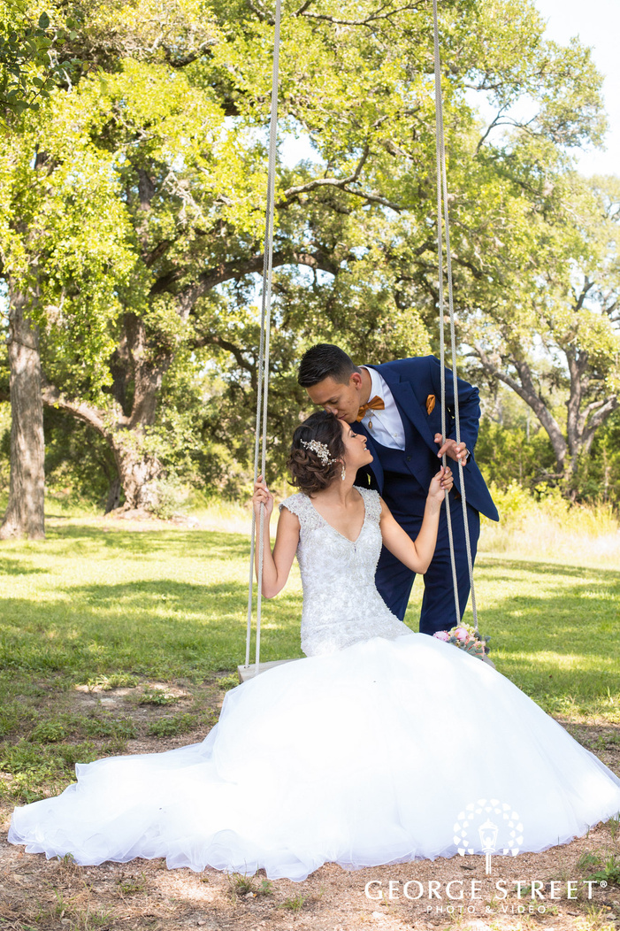 pecan springs ranch austin beautiful sunny outdoor bride and groom swing portraits