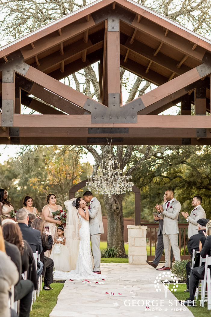 bride and groom first kiss of ceremony gabriel springs austin wedding photos