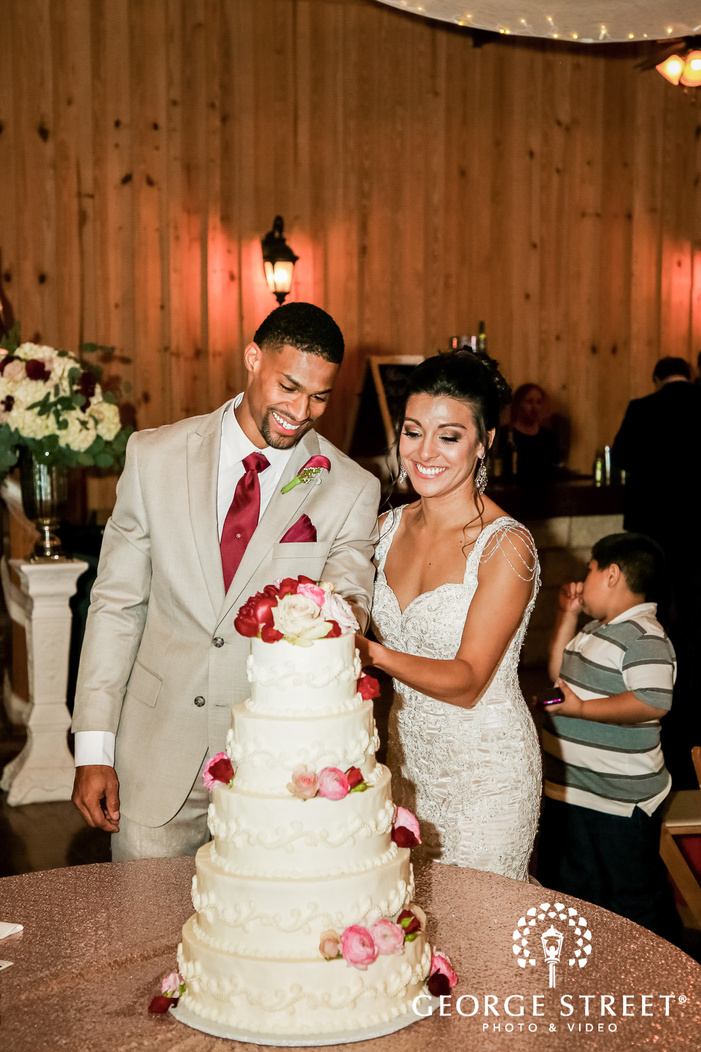 happy couple cutting cake on reception gabriel springs austin wedding photos