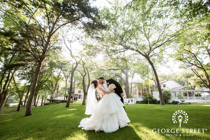 loving bride and groom in green pasture and trees at casa blanca on brushy creek in austin