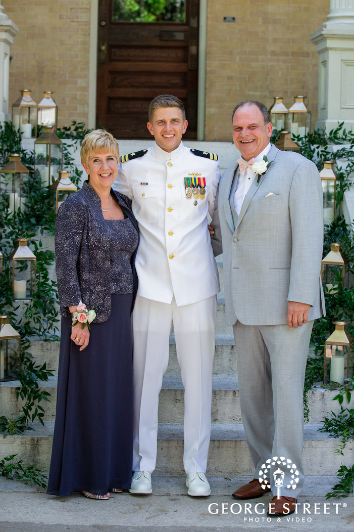 happy groom and parents on steps at entrance wedding photography