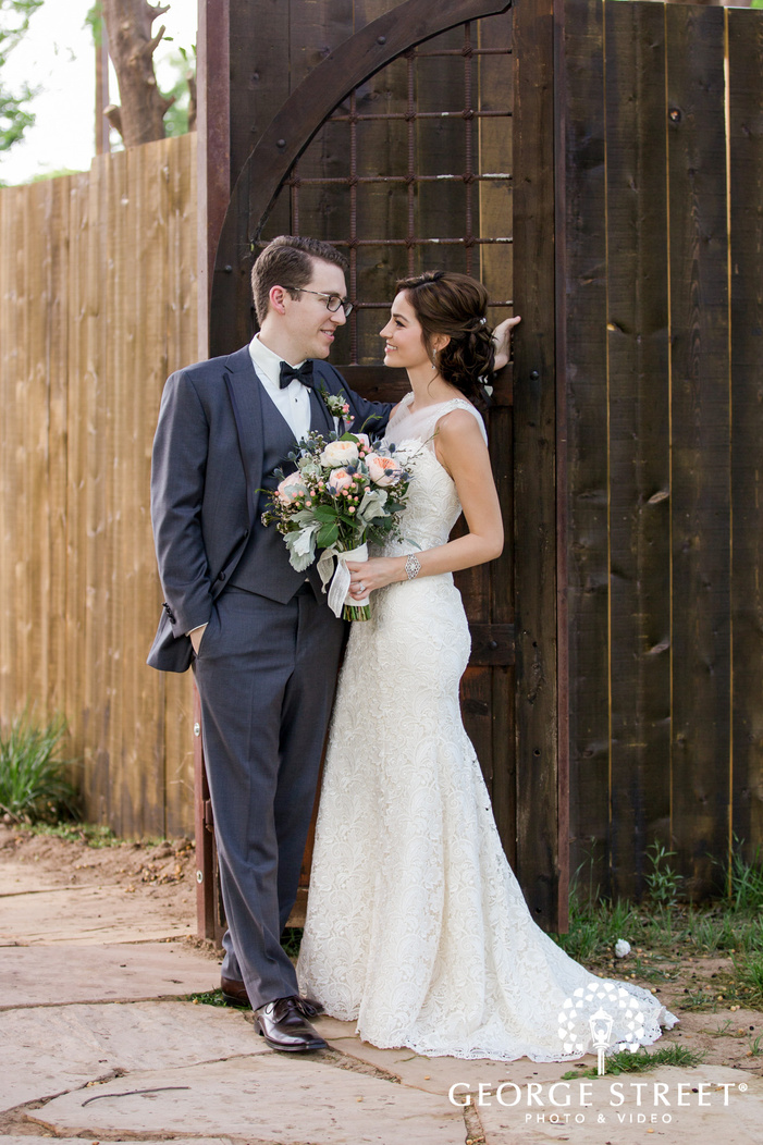 adorable bride and groom near wooden door at venue at the grove in phoenix