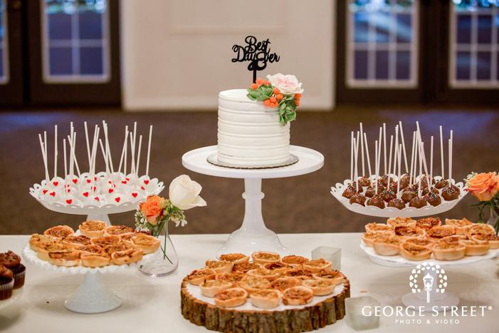 delightful white flower wedding cake and desserts table wedding photo