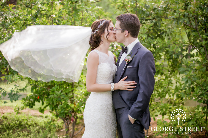 romantic bride and groom in front of green bushes wedding photography