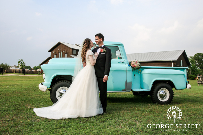 loving bride and groom with truck in front of lone oak barn in austin