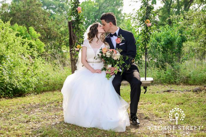 romantic bride and groom on swing at lone oak barn in austin
