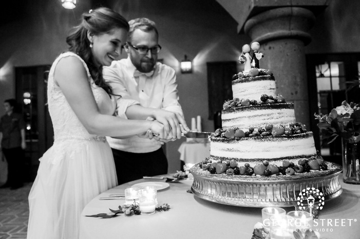 charming bride and groom at cake cutting ceremony